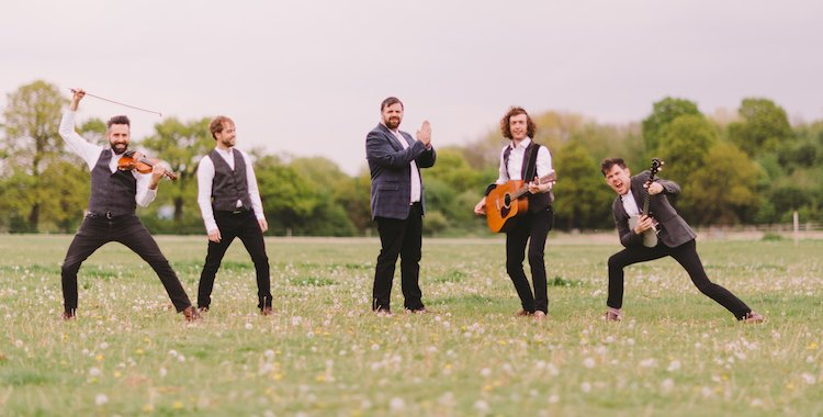 folk style band in a field rocking out