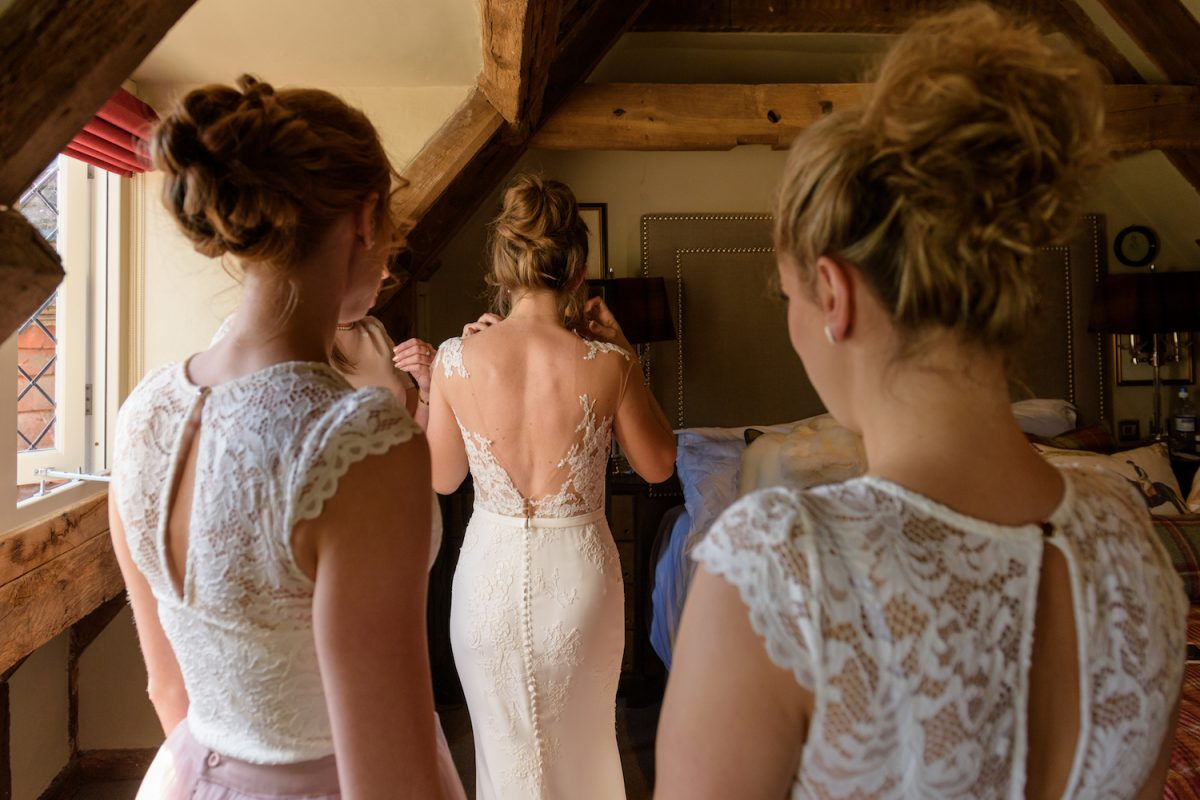 bride putting on wedding dress with bridesmaids