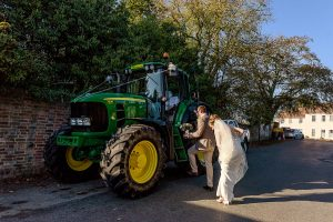 bride and groom getting into tractor